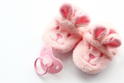 Rosa Babyschuhe und Schnuller.