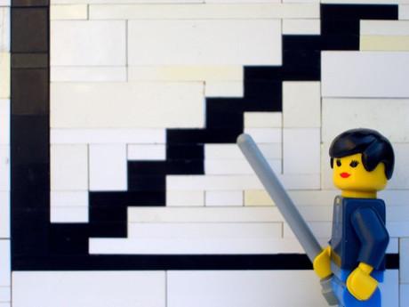Legofigur, die mit einem Zeigestab auf ein Liniendiagramm zeigt.