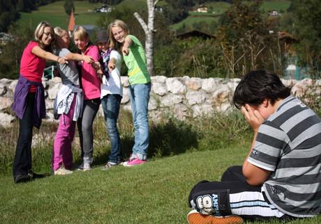 Eine Gruppe Jugendlicher grenzt einen Jungen aus.