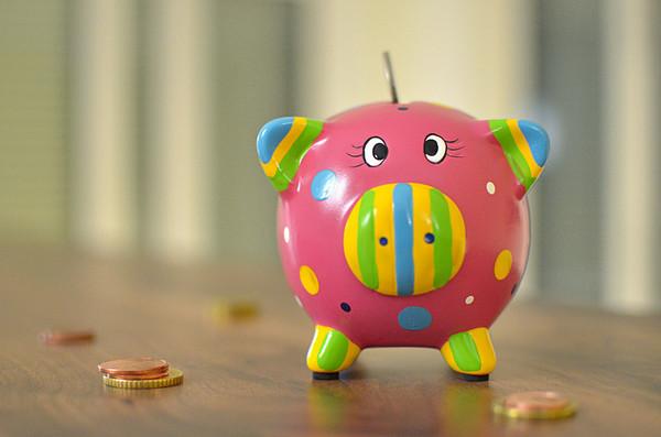 Buntes Sparschwein mit Münze im Schlitz.