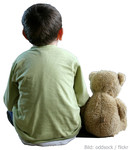 Kleiner Bub von hinten sitzt neben Teddybär.