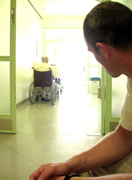 Jugendlicher schaut auf Mann im Rollstuhl.
