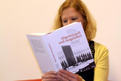 """Frau liest das Buch """"Abgestempelt und ausgeliefert""""."""