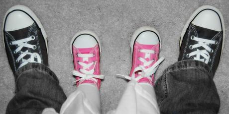 Füße eines Kindes neben den Füßen eines Erwachsenen.