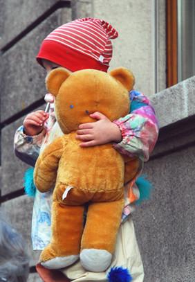 Kleinkind drückt Teddy an die Brust.