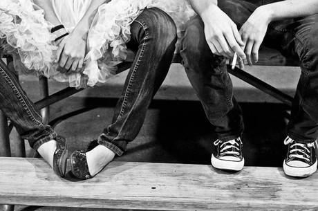 Beine zweier Teenager, die Person rechts hat eine Zigarette in der Hand.