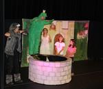 """Szenenbild: Der Froschkönig, Anna, """"Wolferl"""" und zwei Kinder stehen um den Brunnen."""