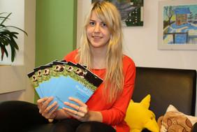 Junge Frau mit der Broschüre der kija Salzburg in der Hand.