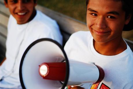 Ein junger Bursch mit Megaphon in der Hand lächelt in die Kamera.