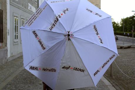 """Weißer Schirm mit Schriftzug """"Asyl""""."""