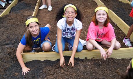 Drei Mädchen sitzen in einem Beet und spielen mit der Erde