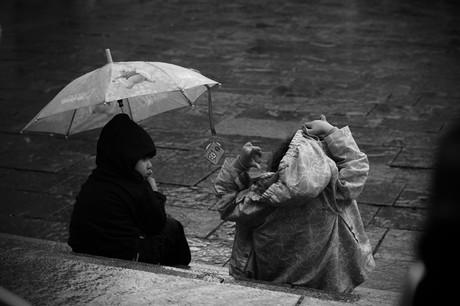 Foto zweier Kinder, die im Regen sitzen.