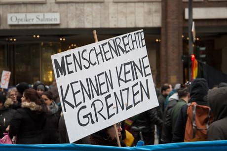 """Bild eines Protestes gegen Abschiebungen, auf dem Transparent steht """"Menschenrechte kennen keine Grenzen""""."""
