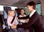 Frau mit zwei gut gesicherten Kindern im Kindersitz im Auto.