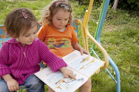 Zwei Mädchen schauen sich ein Bilderbuch an.