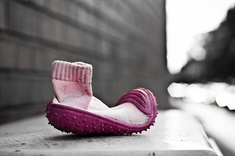 Rosaroter Kinderschuh auf der Straße.