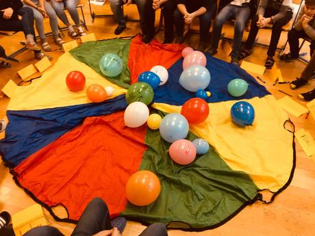 Foto eines großen textilen Netzes, darauf liegen Luftballons