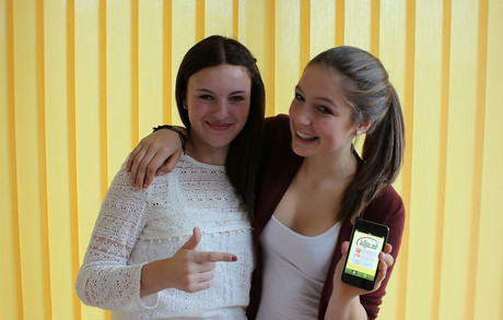 Zwei Mädchen zeigen die App der KIJAS auf dem Smartphone her.
