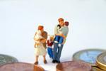 Eine Miniaturfamilie umgeben von riesigen Euromünzen.
