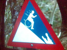 Verkehrsschild mit einem Rollstuhlfahrer, der bergab fährt.