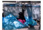 Ein Kind umgeben von Müllsäcken.