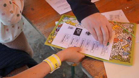 Foto von Händen, eine stempelt gerade den Teilnahmepass am Weltkindertag.