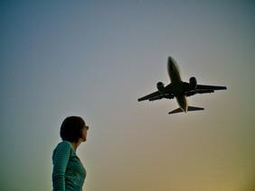 Mädchen blickt Flugzeug nach.
