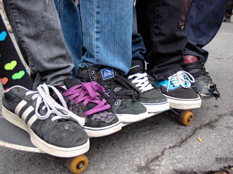 Unterschiedliche Schuhe auf einem Skateboard.