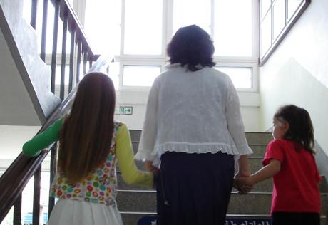 Zwei Mädchen mit Betreuungsperson in einer Schule.