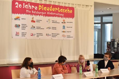 Vier der Kinder aus der Plaudertaschen-Redaktion bei der Pressenkonferenz, hinter ihnen ist das Plakat, auf dem alle Institutionen genannt werden, die hinter der Plaudertasche stecken.