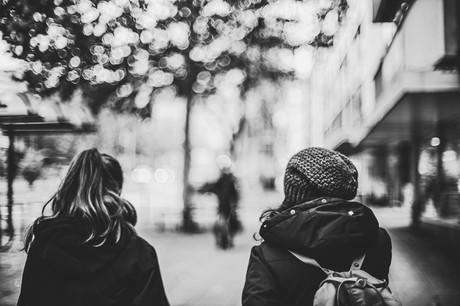 Schwarz-weiß-Bild von zwei jungen Frauen von hinten, die eine Straße entlanggehen.