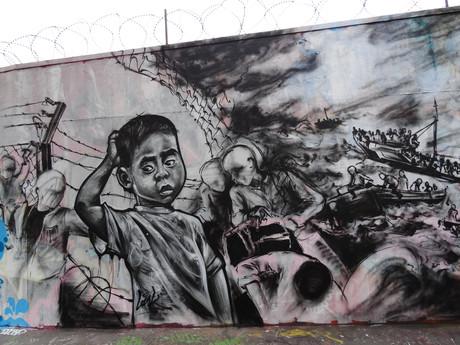 Street-Art - Bilder von Krieg und Flucht auf einer Mauer.