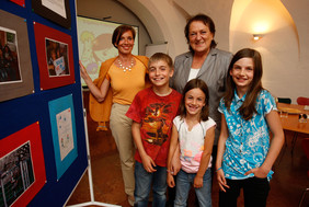 TeilnehmerInnen des Bilderwettbewerbes vor der Ausstellungswand.