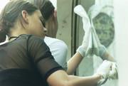 Ein Mädchen putzt eine Fensterscheibe.