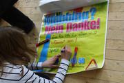 Eine Schülerin setzt ihre Unterschrift auf ein Plakat gegen Mobbing.
