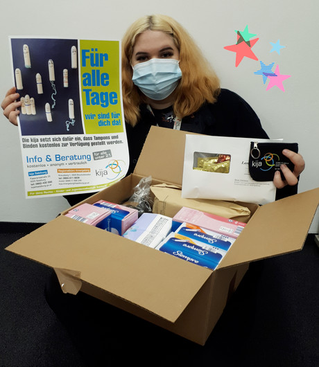 Lehrling Sarah mit einer Schachtel gefüllt mit Hygieneprodukten und dem Poster zur Aktion.