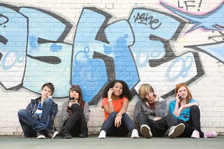 Junge Menschen mit Handys sitzen enlang einer Mauer.