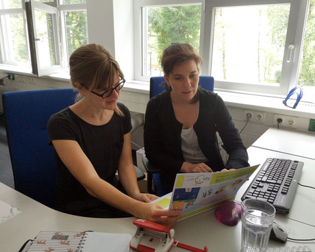 Foto von Veronika Weis und Joanna Wiseman, die gemeinsam den Tätigkeitsbericht durchblättern.