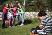 Eine Gruppe Jugendlicher verspottet einen Jungen.