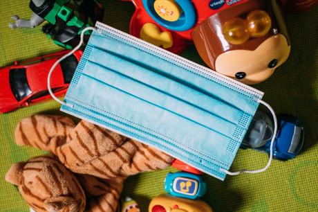 Foto eines Mund-Nasen-Schutzes, der auf Spielsachen liegt.