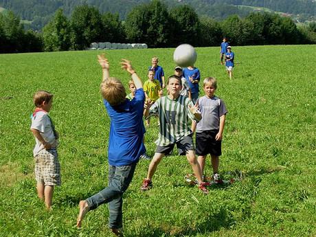 Kinder spielen auf einer Wiese Ball.