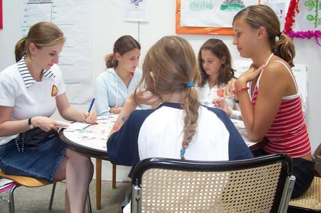 Mädchen sitzen um einen Tisch.