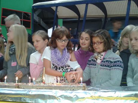 Kinder schneiden eine riesige Torte an.
