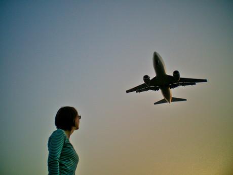 Junge Frau schaut zu einem Flugzeug hoch.
