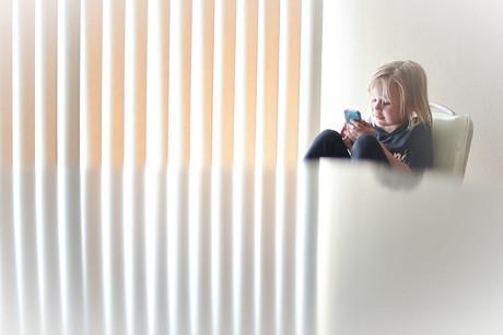 Mädchen mit Smartphone, vor ihr eine große Tischplatte.