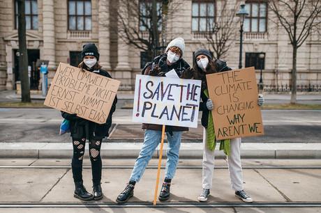 Drei junge Frauen protestieren für mehr Klimaschutz, sie halten jeweils ein Schild in der Hand.