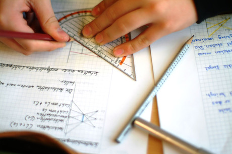 Bild von Kinderhänden, einem Geodreieck und einem Schulheft.