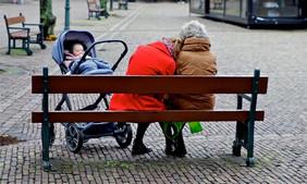 Zwei Frauen sitzen auf einer Parkbank, davor steht ein Kinderwagen mit Baby