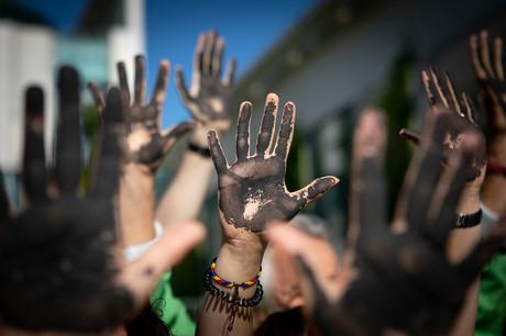 Foto von schwarz bemalten Händen bei einem Protest.