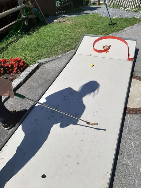 Schatten einer Spielerin auf der Minigolf-Bahn.